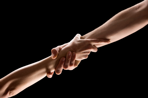 Two hands clasping each other against a black background